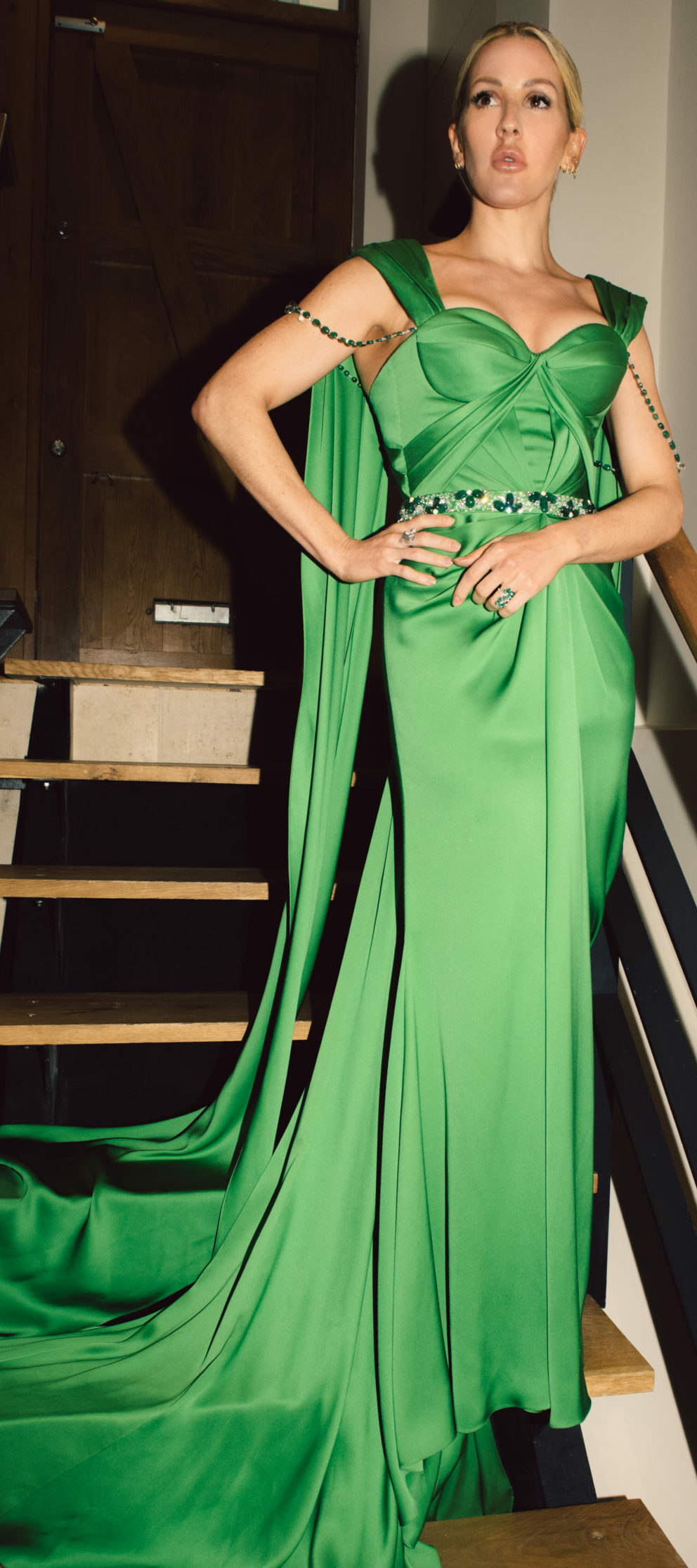 Ellie Goulding standing on stairs in dress green dress featuring Zambian emeralds from Ralph and Russo in Collaboration with Gemfields
